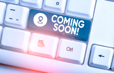 Writing note showing Coming Soon. Business concept for event or action that will happen after really short time White pc keyboard with note paper above the white background