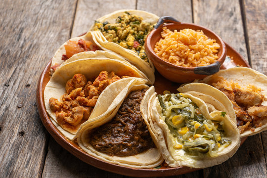 "Mexican stew tacos also called ""guisados"" with rice on wooden background"