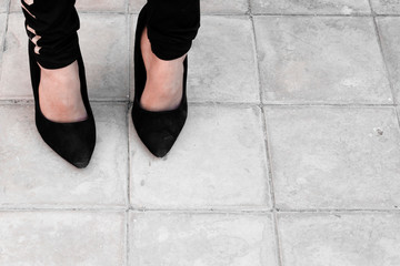 12 years old girl wearing mother big shoes. A little girl in black oversized high heel shoes