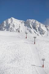 Fototapete - Using ski lift to get to the top of ski slopes