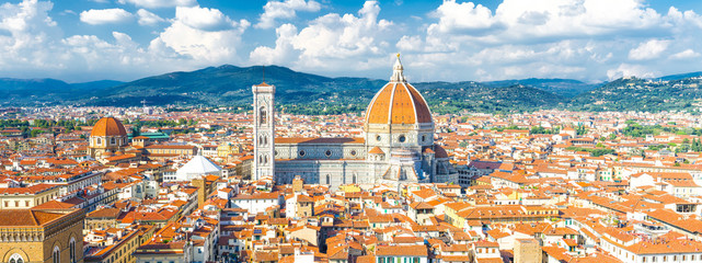 Fototapeten Florenz Top aerial panoramic view of Florence city with Duomo Cattedrale di Santa Maria del Fiore cathedral, buildings houses with orange red tiled roofs and hills range, blue sky white clouds, Tuscany, Italy