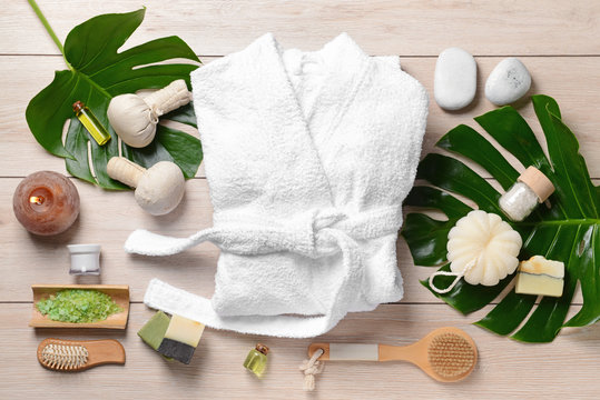Clean bathrobe with spa supplies on wooden background