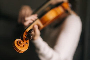 Beautiful woman musician plays the violin in her home, close-up. Female 's face is not visible.