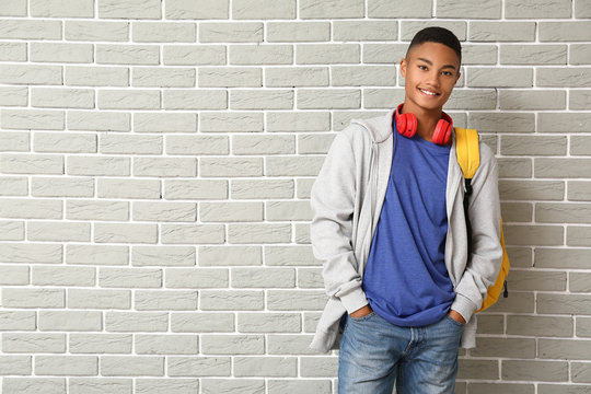 Portrait of African-American teenage schoolboy on brick background