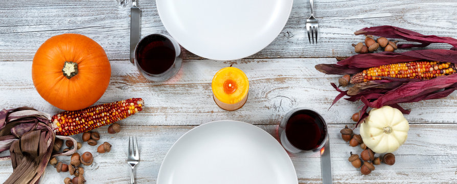 White dinner table decorated for Thanksgiving celebration