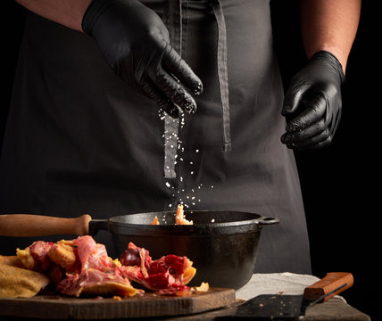 chef in black uniform and latex gloves sprinkles with white salt raw chicken meat in a black cast-iron frying pan, cooking