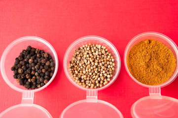 Spices: black pepper, ground red pepper and coriander peas in jars on a red background