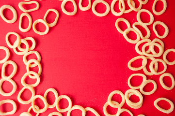 Frame of onion ring chips on red background