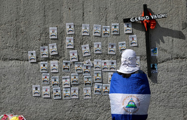 A demonstrator wearing the national flag looks at pictures of protesters who died during the protests against Nicaraguan President Daniel Ortega's government last year in Managua