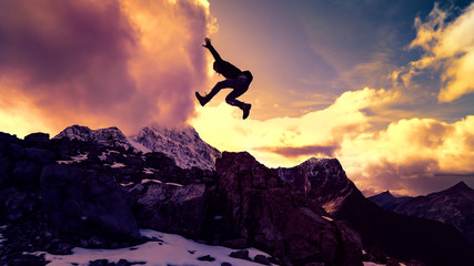 Victorious Young Man Leaping On Epic Mountain Peak Success Concept