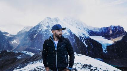 Man Standing On Winter Mountain Peak Snow Fall Male Model Adventurer