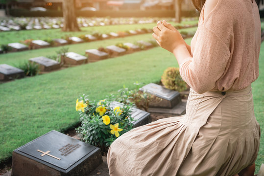 Close-Up of Religious Christian Woman Hands Clasped While Honoring and Praying to Military in War Cemetery. Teenager Woman in Expression Sadness and Pray for Soldier Prisoner of War in Tomb.