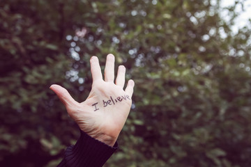 Womans hand raised with I believe written in marker supporting victims of sexual abuse
