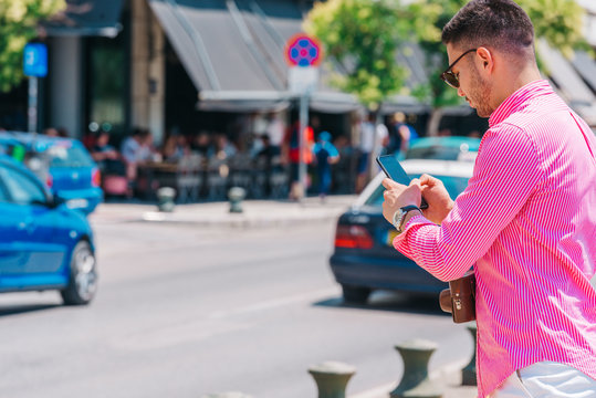 Stylish tourist calling a lift on his smartphone.
