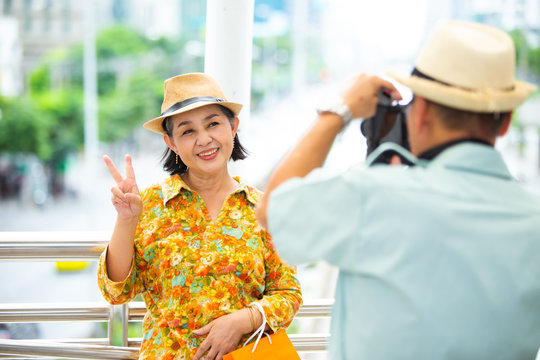 Travel and tourism concept. senior Asian couple with camera and take a photographing in the city with shopping paper bag