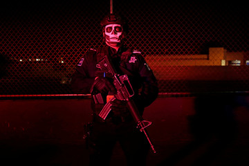 A police officer with his face painted poses for a photograph while watching the Day of the Dead parade in Ciudad Juarez