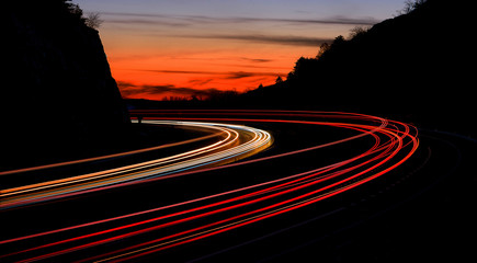 In de dag Nacht snelweg tail light streaks on highway at night. Long exposure.