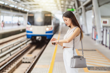 Young Asian woman passenger listening music via smart mobile phone and looking train with Hand watch in subway train station, japanese,chinese,Korean lifestyle, commuter and transportation concept