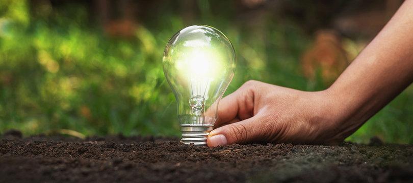 Holding a light bulb on the ground Energy saving concept