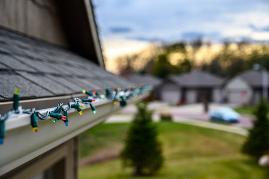 Hanging Christmas lights on gutter edge with plastic clips