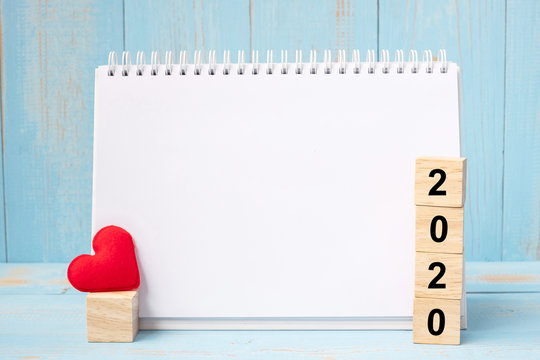 blank notebook and 2020 cubes with red heart shape decoration on blue wooden table background. New Year NewYou, Goal, Resolution, health, Love and Happy Valentine's day concept