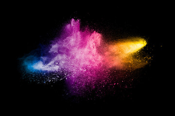 Explosion of colorful Holi powder on black background. Vibrant color dust particles textured background.