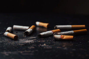 Cigarettes were burnt and smoking.World No Tobacco Day falls on May 31 of every year.Smoke cigarettes were smashed,On black  floor.