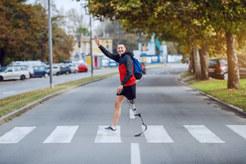 Fotomurales - Full length of handsome caucasian handicapped sportsman in sportswear, with artificial leg and backpack crossing street and waving to a friend.