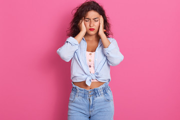 Picture of beautiful young Caucasuian brunette woman wearing glasses, blue shirt and jeans, looks stressed, posing with hand on head, having terrible headache, standing against pink studio wall.