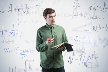 Young man with notebook, science formula