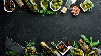 Fotomurales - Olive oil, olives and spices on a black stone background. Top view. Free space for your text.