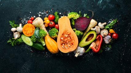 Foto op Plexiglas Keuken Fresh seasonal vegetables on a black stone background: Pumpkin, tomato, avocado, cucumber, onion, carrot. Autumn food. Top view. Free copy space.
