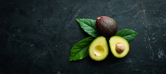 Fresh avocado with leaves on a black background. Top view. Free space for your text. Papier Peint