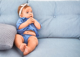 Adorable baby lying down on the sofa at home. Newborn relaxing and resting comfortable