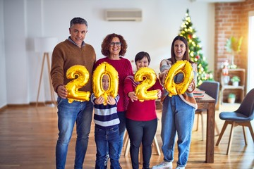 Beautiful family smiling happy and confident. Standing and posing holding 2020 balloons celebrating new year around christmas tree at home