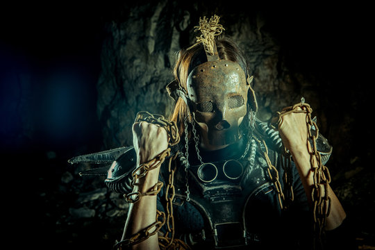 Post-apocalyptic woman in the rusty skull mask on the dungeon background. Nuclear post-apocalypse time. Life after doomsday