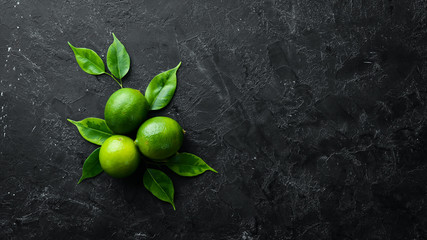 Fresh green limes with leaves. Citrus fruits. On a black stone background. Top view. Free space for your text. Wall mural