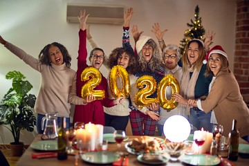 Beautiful group of women smiling happy and confident. Posing around christmas tree holding 2020 ballons at home