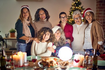 Beautiful group of women smiling happy and confident. Posing around christmas tree at home
