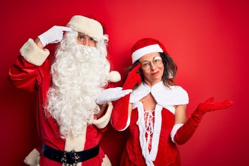 Middle age couple wearing Santa costume and glasses over isolated red background confused and annoyed with open palm showing copy space and pointing finger to forehead. Think about it.