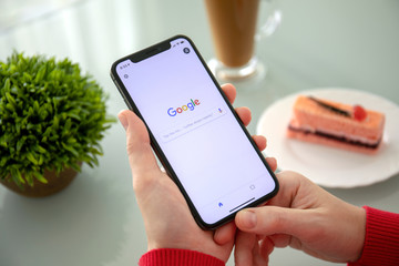 Woman holding iPhone X with social networking service Google
