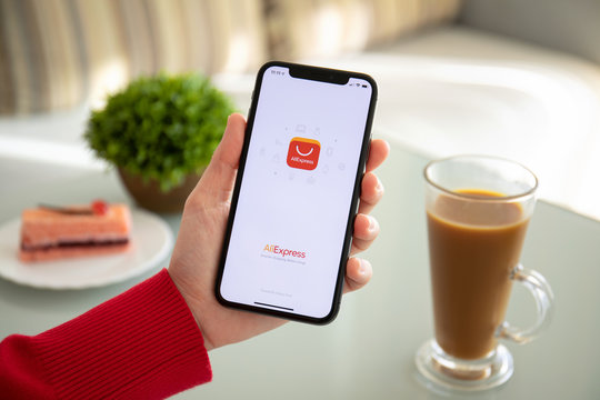 Woman holding iPhone X with Internet shopping service Aliexpress