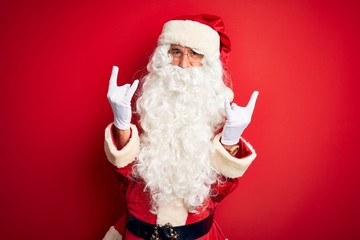 Middle age handsome man wearing Santa costume standing over isolated red background shouting with crazy expression doing rock symbol with hands up. Music star. Heavy music concept.