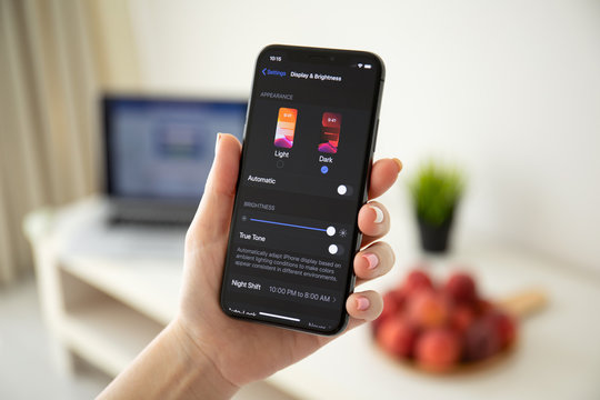 Woman hand holding iPhone X with IOS 13 Dark Mode.