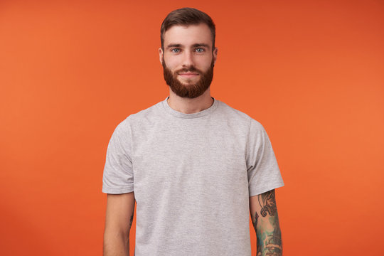 Attractive young bearded tattooed brunette man with trendy haircut standing over orange background, keeping hands along body and looking at camera with charming smile