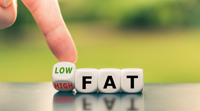 """Hand turns a dice and changes the expression from """"high fat"""" to """"low fat""""."""