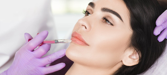 woman having lip injections, a prick of a syringe for the beauty lips. lip augmentation