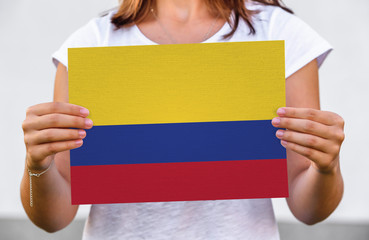 woman holds flag of Colombia on paper sheet