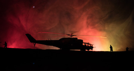 Silhouette of military helicopter ready to fly from conflict zone. Decorated night footage with...