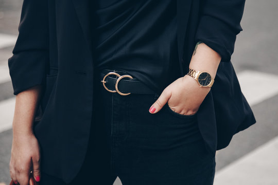 street style 2019 fashion details. close up, young fashion blogger wearing black jeans, satin top, blazer and a black and golden analog wrist watch.